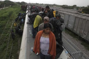 Central American migrants ride on top of a northern bound train durin