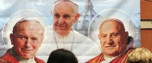 A woman take a picture of an illustration depicting Pope John Paul II, Pope Francis and Pope John XXIII outside a shop in Rome